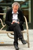 geoffrey rush texting on his cell phone as he sits
