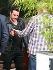Antony Costa being shown a prosthetic bionic arm,...