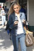 Joanna Krupa checks her mobile phone while out...