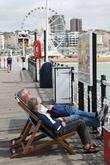Sunbathers enjoy the sunny weather in Brighton Sussex,...