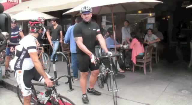 Ethan Suplee speaks to photographers as he takes a break from riding his bike