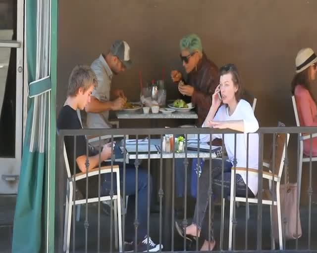 Casually Dressed Milla Jovovich Talks On Phone During Breakfast Date With Friend