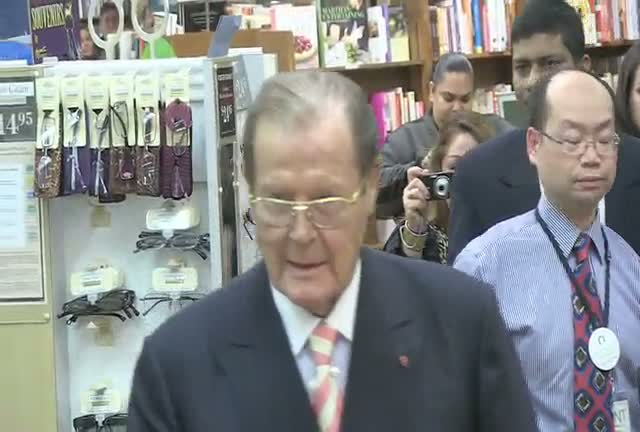 Sir Roger Moore Meets Young Bond Fan At 'Bond On Bond' Book Signing