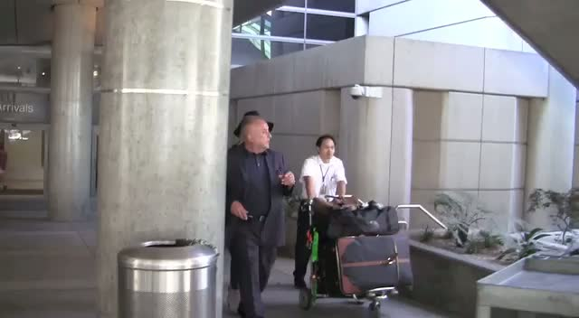 Rosie Huntington-Whiteley Is Escorted To Her Car At LAX