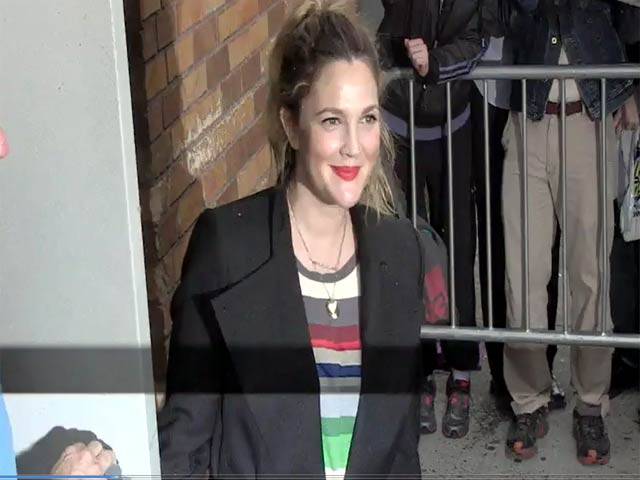 Drew Barrymore Tries To Keep Dry As She Greets Photographers Outside 'The Daily Show'